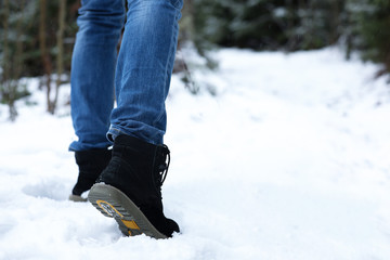 Woman walking outdoors on snowy day, closeup with space for text. Winter vacation