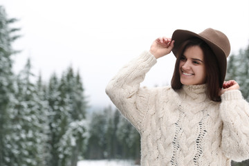 Young woman in warm sweater near snowy forest, space for text. Winter vacation