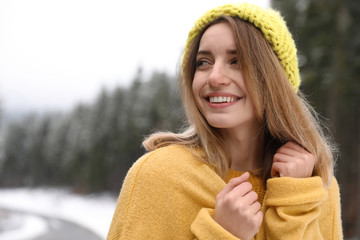 Young woman in warm clothes outdoors. Winter vacation