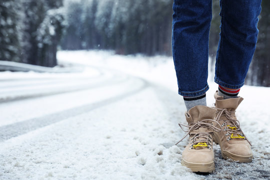 Woman walking outdoors on snowy winter day. Space for text