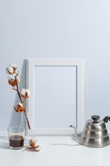 Mock up white frame, dry cotton twigs in vase and coffee pot on book shelf or desk. White-blue colors. Minimalistic concept.