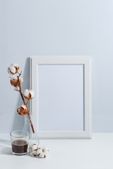Mock up white frame, dry cotton twigs in vase and coffee cup on book shelf or desk. White-blue colors. Minimalistic concept.