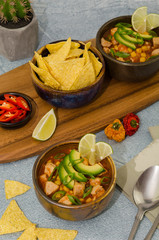 Pozole with corn, stew from Mexico. Spicy tortilla soup with pork, cilantro, tomatoes, avocado and corn