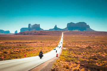 Wall Mural - Biker on Monument Valley road at sunset, USA