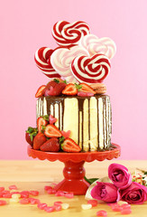 St Valentine's Day on-trend candyland fantasy drip novelty cake decorated with heart shaped lollipops, candy and fresh strawberries.