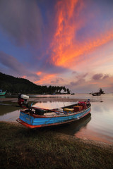 Small fishing boats moored beached on the beach during sunset and the beautiful natural of the colorful sky at Mae Ramphueng Beach Bang Saphan District , Prachuap Khiri Khan province in Thailand.
