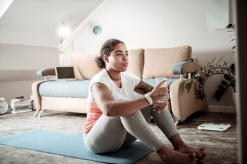 African American curly lady sitting on yoga mat and drinking water