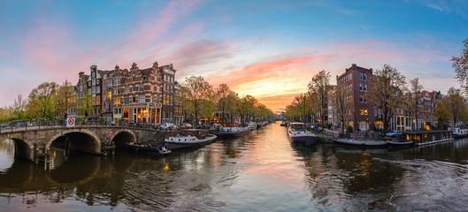 Obraz Amsterdam Netherlands, sunset panorama city skyline at canal waterfront - fototapety do salonu