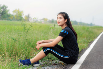 Girl is sitting on road.