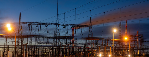 Electrical substation at night,in the background smoking power plant chimneys