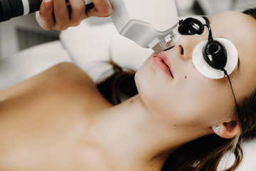 Close up photo of a woman with glasses laying on bed in a salon. Young woman doing laser epilation on face.