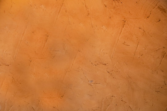Organgish rough stucco mud grunge background where you can see the marks where it been applied