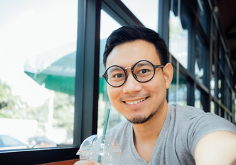 Man with glasses selfy himself drink coffee in the cafe.