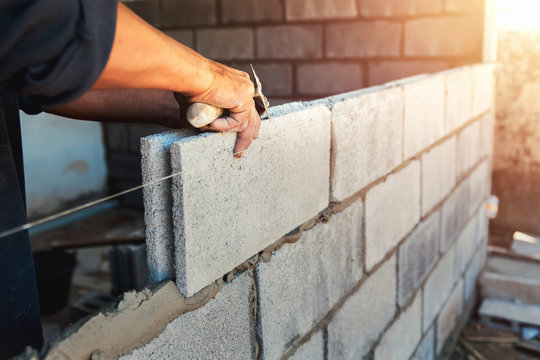 Worker building wall bricks with cement