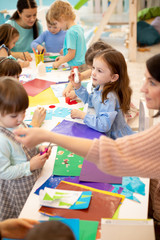 Art and craft activity in the kindergarten. Group of preschool kids hands working in daycare center.