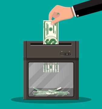 Hand putting dollar banknote in shredder machine