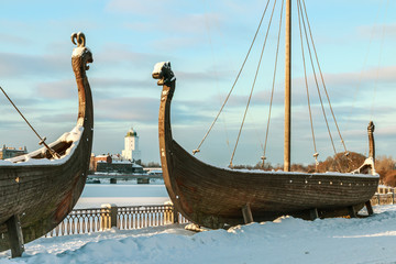 Drakkar ships and Vyborg castle in winter in the background against the blue sky. Focus on the castle