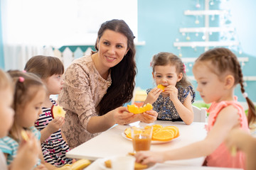 Children and carer together eat fruit as a snack in the kindergarten, nursery or daycare