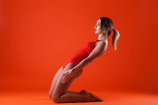 young beautiful dancer in orange swimsuit posing on isolated red studio background