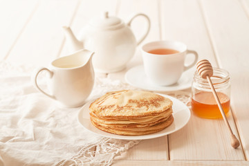 Pancake week:  pancakes with honey and tea on the table