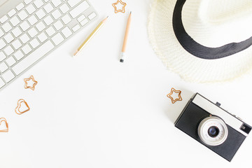 Flat lay top view business desk mockup: pencils, straw hat, photo camera and keyboard on white background. Clean and bright. Travel, business concept. Text space