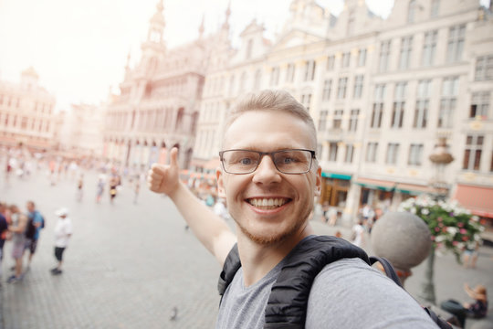 Happy man student with backpack taking selfie photo on central square Brussels, Belgium