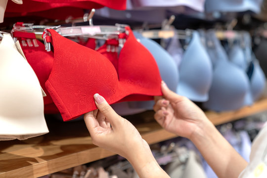 Close up of hands choosing bras cups size and looking light new wireless and seamless technology with red hot color and sexy bra in lingerie shop at department store. Woman shopping underwear concept.