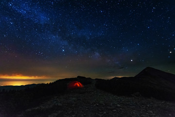 Night sky with a chuvash way on the background of mountains and illuminated red tent.