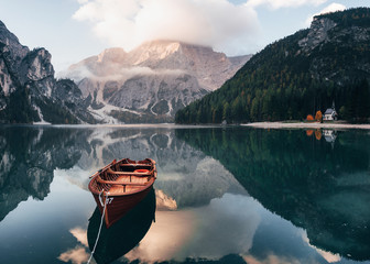 Its sunlight on the peak. Wooden boat on the crystal lake with majestic mountain behind. Reflection in the water. Chapel is on the right coast Fototapete