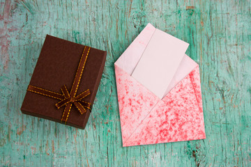 top view present box and evelope with  white blank paper sheet with place for text on a mint green shabby background
