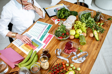 Dietitian writing a diet plan, view from above on the table with different healthy products and drawings on the topic of healthy eating Wall mural