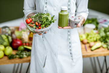 Nutritionist in medical gown holding salad and smoothie drink with healthy food on the background, close-up view with no face