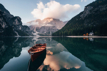 Clouds is on the top. Wooden boat on the crystal lake with majestic mountain behind. Reflection in the water. Chapel is on the right coast