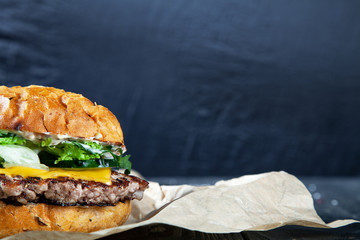 Close up view on burger with meat, sauce and greens on craft paper on a dark background. Delicious snack. American fast-food. Copy free space for logo, text. Picture for recipe