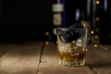 Car keys in a glass with an alcoholic drink on a wooden background. Drunk driving concept, stop drinking and driving.