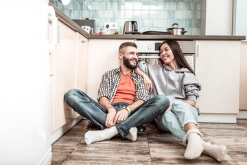 Young couple wearing jeans sitting on the floor near cooker