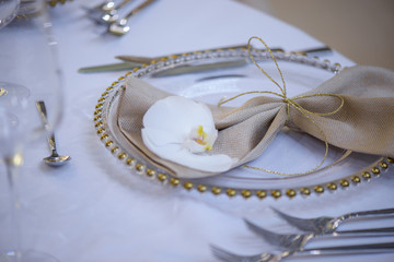 Fine dining table setting featuring transparent plates, beige linen napkin with natural orchid and golden decorations and silverware in the order of use, ready for guests at a formal event or wedding