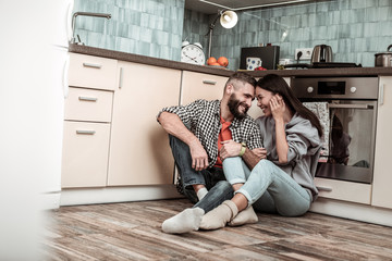 Loving couple feeling memorable while sitting in the kitchen