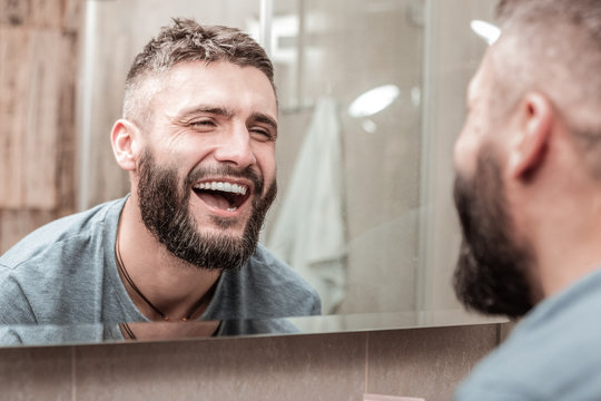 Happy joyful man looking at his face in the mirror