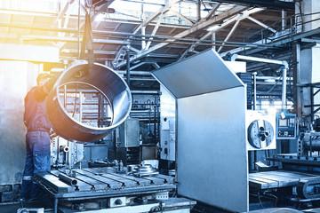Metal industry: a worker prepares a valve part