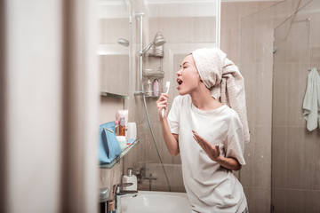 Delighted positive woman singing in the bathroom