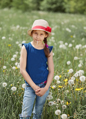 little girl in a straw hat,standing on a green meadow