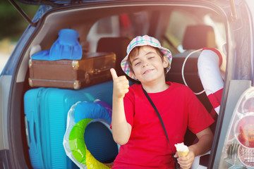 Wall Mural - child sitting in car filled with traveling accessories