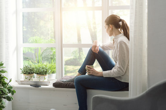 Woman relaxing at home and having coffee