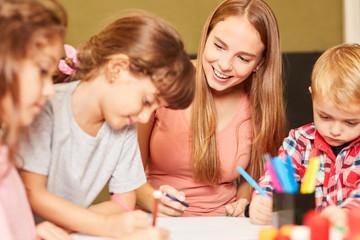Kinder und Kindergärtnerin malen zusammen