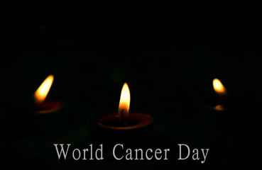 World Cancer Day concept: the candles burn brightly on the dark background