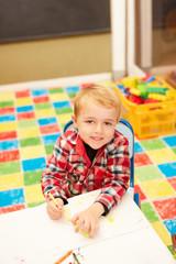 Lächelnder Junge malt Bilder mit Buntstiften