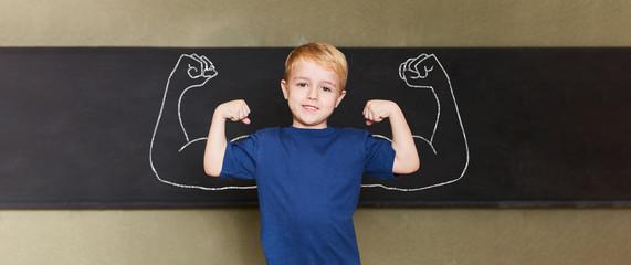 Selbstbewusstes Kind mit Muskeln vor Tafel