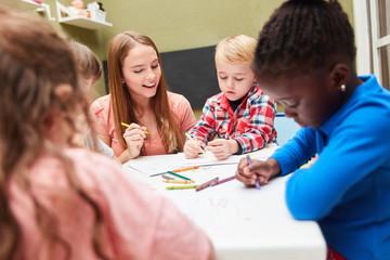 Gruppe Kinder malt mit Filzstiften Bilder