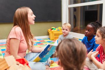 Kinder und Kindergärtnerin beim Vorlesen